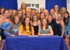 Members of the Columbus North girls' swimming team surround Marah Bieger (seated, West Virginia shirt) and Maddie Wyke (seated, Ohio University shirt) during a NLI signing ceremony on Wednesday, Nov. 12.