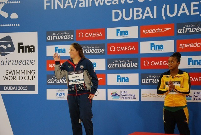 Molly Hannis waiving as she steps on the podium, with Alia Atkinson looking on.